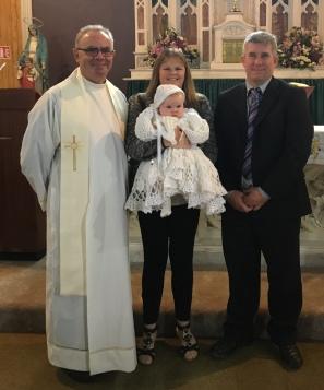 Elisabeth Rita Hanrahan on her baptism day with her parents Jennifer and Anthony on her baptism day.