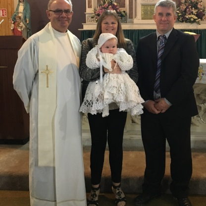 Elisabeth Rita Hanrahan on her baptism day with her parents Jennifer and Anthony on her baptism day.